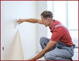 Man placing wallpaper on a wall